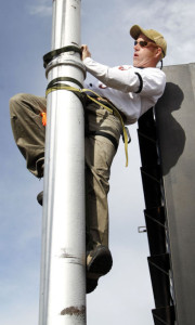 Ty Graham uses a harness and straps to make his way up the flag pole on the Black's Building to install a new pulley Monday, Oct. 14, 2013, in downtown Waterloo, Iowa.